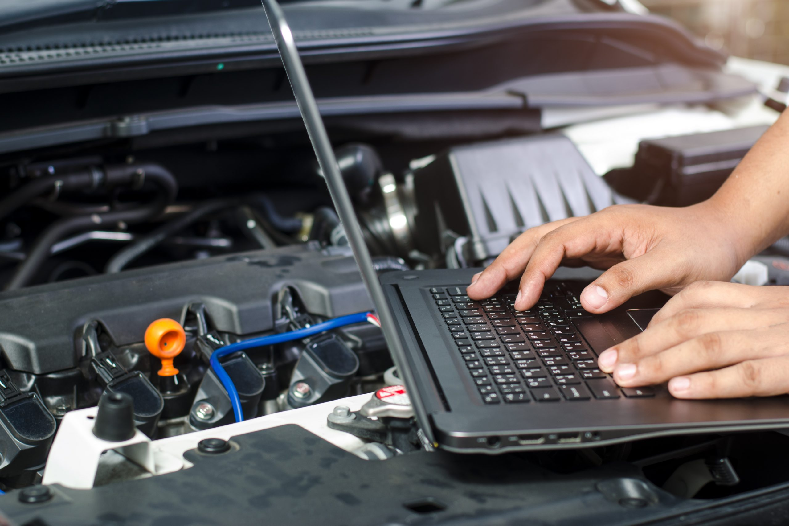 mechanic using electronic diagnostic equipment to tune a car adobe stock image